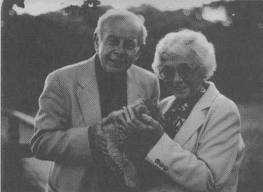 black and white photo of man and woman holding cat